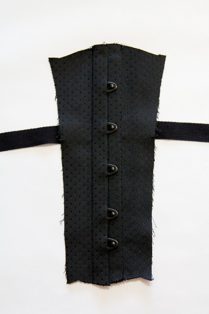 A corset busk inserted into spot coutil © Amy Earl